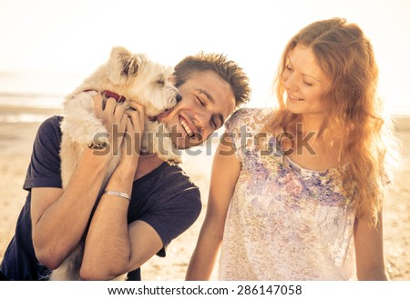 couple walking with dog outdoor. man holding up the cute dog while he licks his face - stock photo