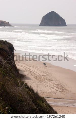 Couple Walks Blustery Day Bluffs Seaside Oregon Coast Pacific Ocean - stock photo