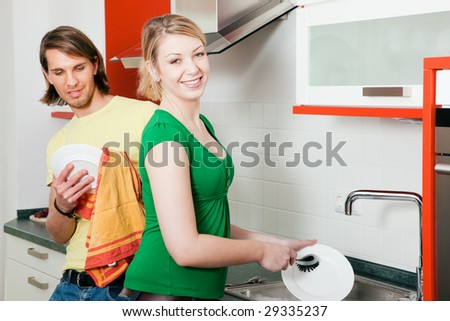 Couple washing their dishes in a kitchen sink