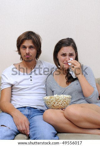 Couple watch a movie at home with popcorn - stock photo