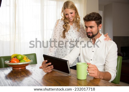 Couple watching a video on the internet while having breakfast - stock photo