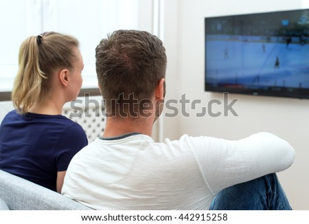 Couple watching hockey match on tv.