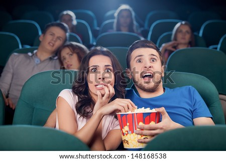 Couple watching horror movie. Terrified people in watching movie at the cinema - stock photo