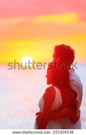 Couple watching romantic sunset during beach holidays. Newlyweds in a happy relationship at sunset during travel holidays vacation getaway. Interracial couple, Asian woman, Caucasian man. - stock photo