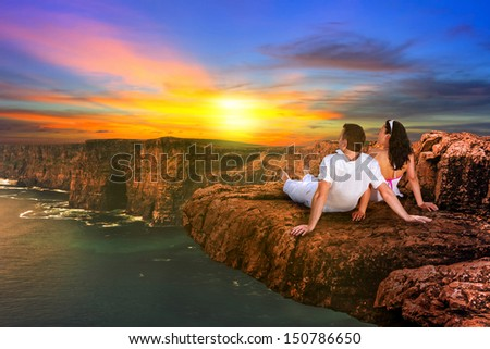 Couple watching sunset on the edge of cliff - stock photo
