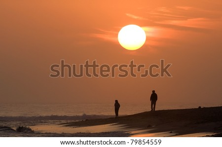 Couple watching sunset over the Pacific Ocean - stock photo