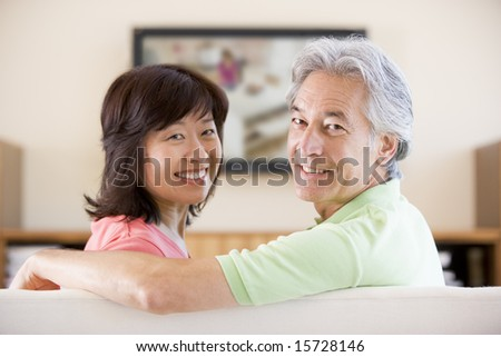 Couple watching television smiling - stock photo