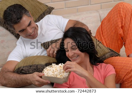 Couple watching tv and eating popcorn. Couple sharing in a living room.
