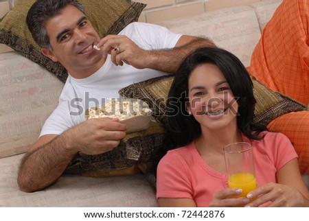 Couple watching tv and eating popcorn. Couple sharing in a living room. - stock photo