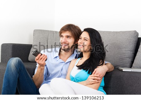 Couple watching tv in their living room at home, young happy smile man and woman sitting on couch, sofa, hold remote control