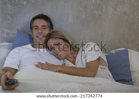 Couple watching TV together in bed