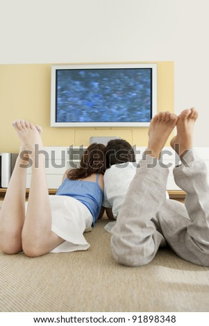 Couple watching tv together while laying down on the floor.