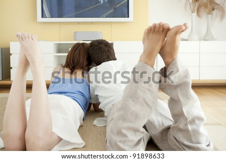 Couple watching tv together while laying down on the floor in living room.