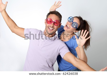 Couple wearing colored glasses having fun on white background - stock photo