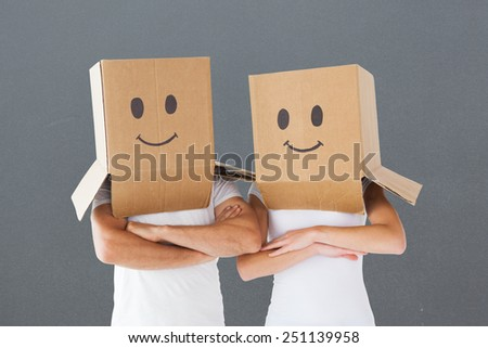 Couple wearing smiley face boxes on their heads against grey - stock photo