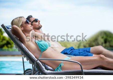 Couple wearing sunglasses and relaxing on a sun lounger near pool - stock photo