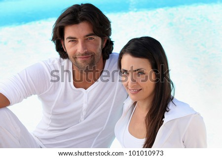 Couple wearing white clothing sat by swimming pool