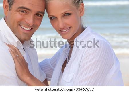 Couple wearing white clothing stood on a beach - stock photo
