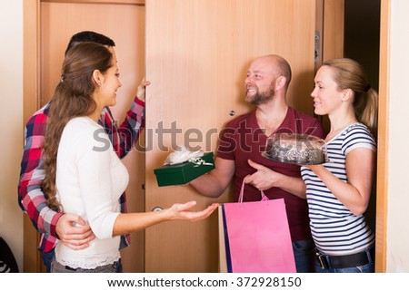 Couple welcomes happy friends at home - stock photo