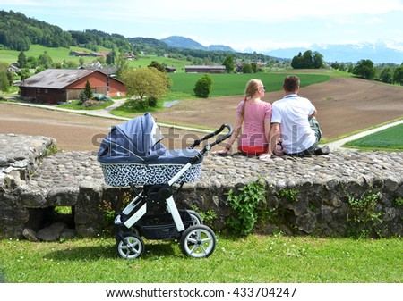 Couple with a baby stroller enjoying Alpine panorama. Switzerland