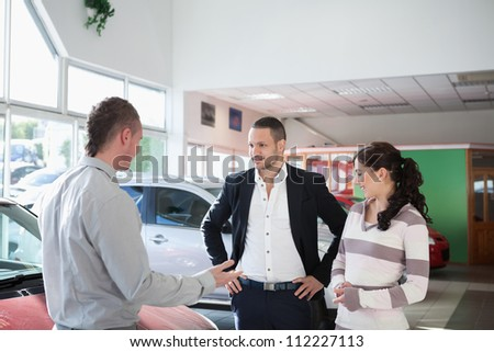 Couple with a car dealer in a car shop