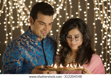 Couple with a tray of diyas - stock photo