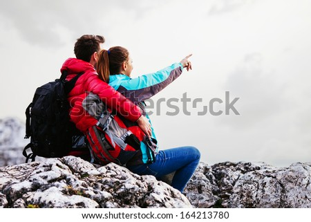 Couple with backpacks in mountains sitting on rocks. - stock photo
