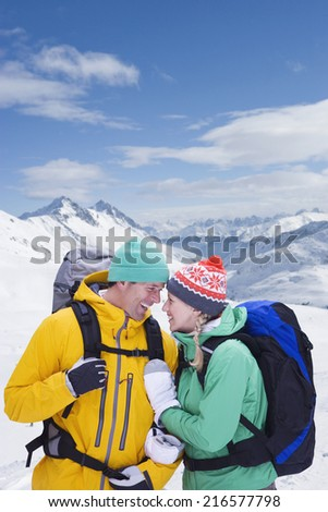 Couple with backpacks smiling face to face on snowy mountain