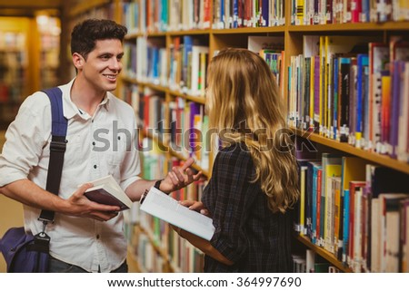 Couple with books looking at each other in the library