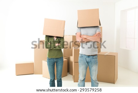 couple with boxes on their heads standing in their new house, arms crossed against their chests
