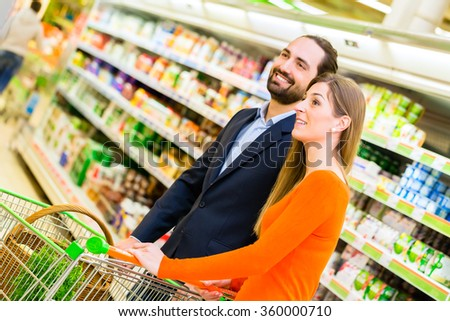 Couple with cart grocery shopping in supermarket  - stock photo