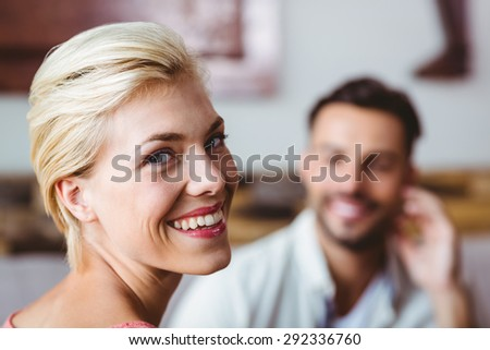 couple with coffee cup sitting on sofa at home
