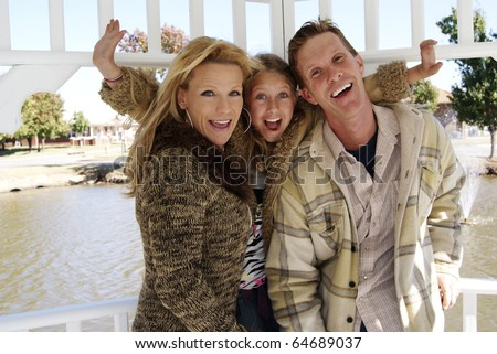 Couple with daughter at park having fun and laughing - stock photo