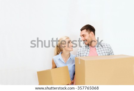 couple with delivery boxes moving to new home - stock photo