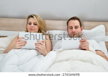 Couple With Digital Tablets In Bed At Home
