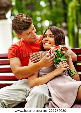 Couple with flower at park on bench. Outdoor. - stock photo