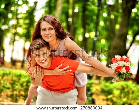 Couple with flower at park. Outdoor. Orange t-shirt. - stock photo