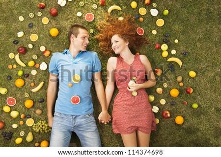 Couple with fruit is lying on the grass - stock photo