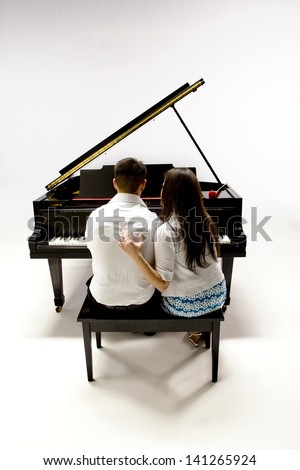 Couple with Grand piano 1 in white shirt, black pants and sundress sitting at piano bench with red rose. - stock photo