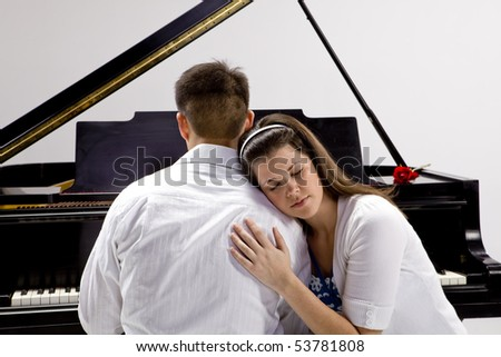 Couple with Grand piano 4 sitting at piano bench with red rose.