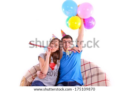 Couple with hats and balloons sitting on the couch  - stock photo