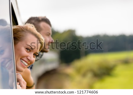 Couple with heads out the train window excited woman man