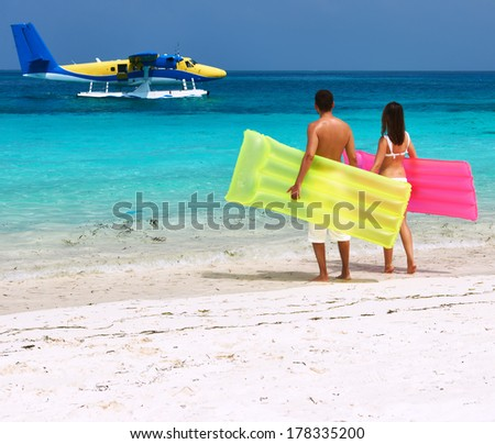 Couple with inflatable rafts looking at arrived seaplane on a tropical beach at Maldives. No brand names or copyright objects - stock photo
