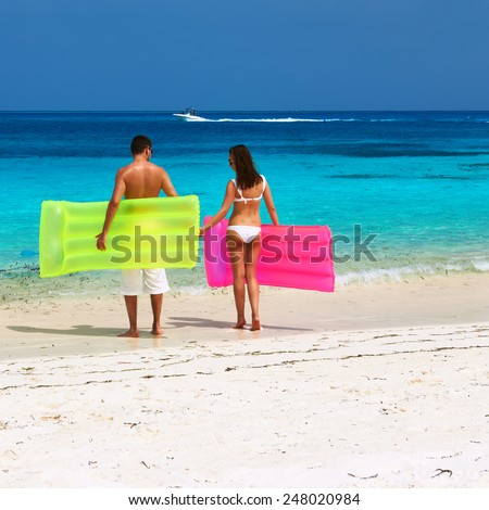 Couple with inflatable rafts on a tropical beach at Maldives - stock photo