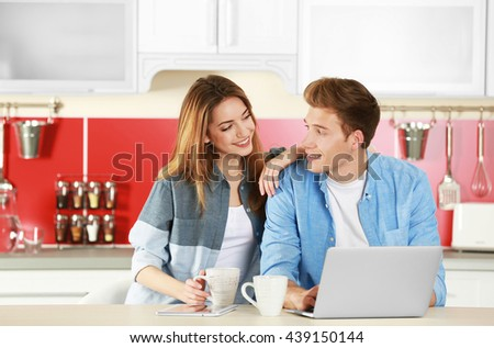 Couple with laptop in kitchen