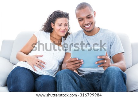 Couple with laptop sitting on sofa at home - stock photo