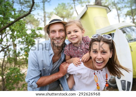 Couple with little girl enjoying vacation in camper van - stock photo
