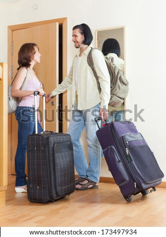 Couple with luggage looking in mirror near door in home