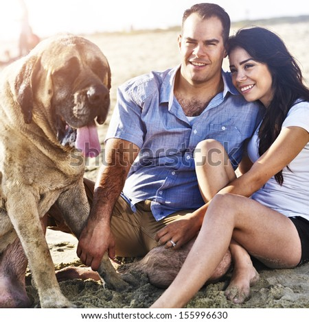 couple with pet dog on the beach - stock photo