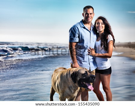couple with pet dog posing on the beach. - stock photo